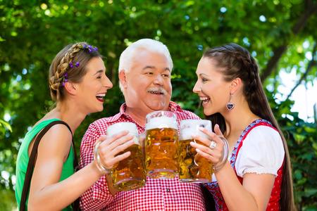 lederhosen: In Beer garden - friends in Tracht, Dirndl and Lederhosen drinking a fresh beer in Bavaria, Germany