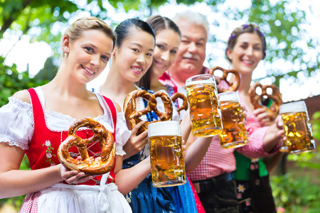 In Beer garden - friends, man and women in Tracht, Dirndl and Lederhosen drinking a fresh beer in Bavaria, Germany Stock Photo - 29284534