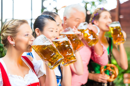 In Beer garden - friends, man and women in Tracht, Dirndl and Lederhosen drinking a fresh beer in Bavaria, Germany Stock Photo - 29284536