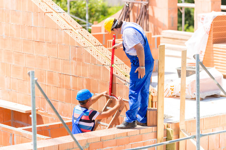 Two builder or worker with helmets controlling walls in scaffold with a bubble level on building or construction site photo