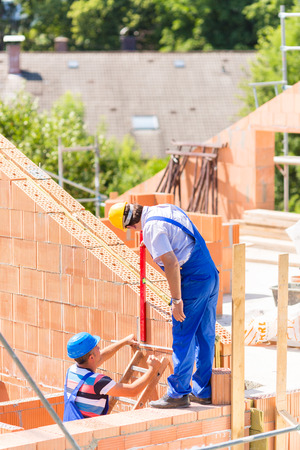 tallyman: Two builder or worker with helmets controlling walls in scaffold with a bubble level on building or construction site