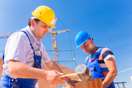 proud: Construction site worker building a home or house doing bricklaying work on the walls of the shell  Stock Photo