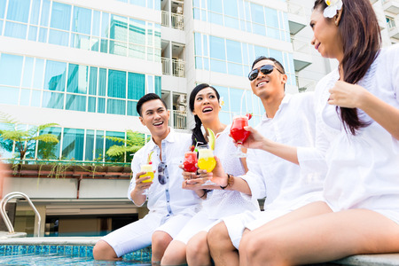 Asian Friends sitting by swimming pool with drinks photo