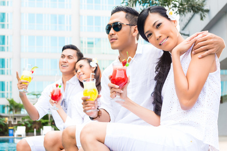 Asian couples drinking cocktails at hotel swimming pool photo
