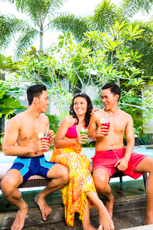 all smiles: Asian friends drinking fancy cocktails at hotel or club pool