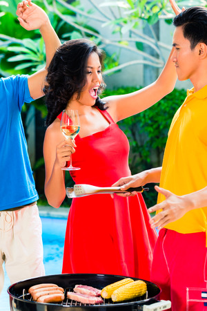 Asian friends celebrating pool party with music, wine and barbecue or BBQ photo