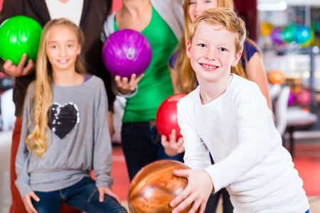 kids activities: Parents playing with children together at bowling center Stock Photo