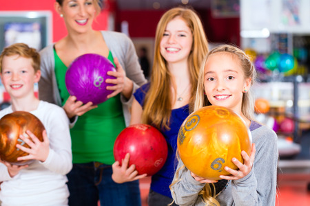 boy ball: Parents playing with children together at bowling center Stock Photo