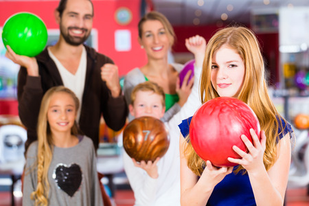 bowling alley: Parents playing with children together at bowling center Stock Photo