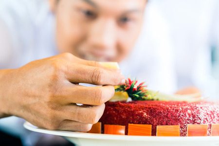 Close up of Asian chef decorating cake photo