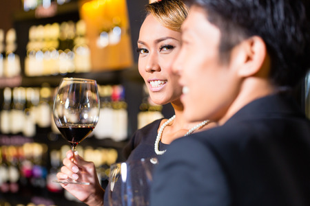 Close up of Asian couple drinking red wine photo