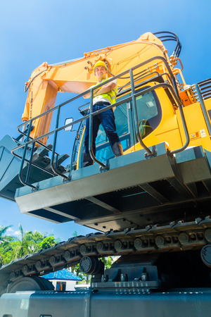 Asian driver standing on construction machinery on building site photo