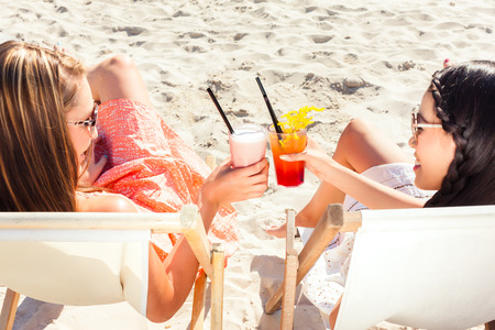 lounger: Two girls or woman drinking cocktails in beach club and sitting on sun lounger