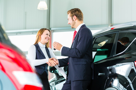 Seller or car salesman and customer in dealership, they shaking hands, hands over the car keys and seal the purchase of the auto or new car Stock Photo