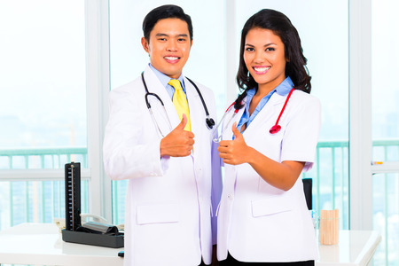 Asian male and female doctor standing proud in his office or medical practice photo