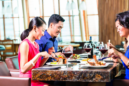 chinese adult: Asian Friends eating and drinking wine in restaurant