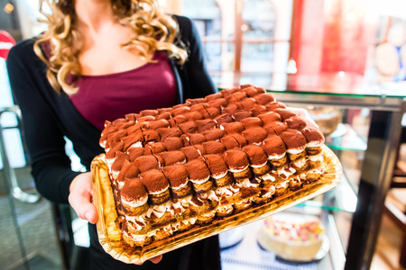 Female confectioner presenting tray of cake in bakery or pastry shop photo