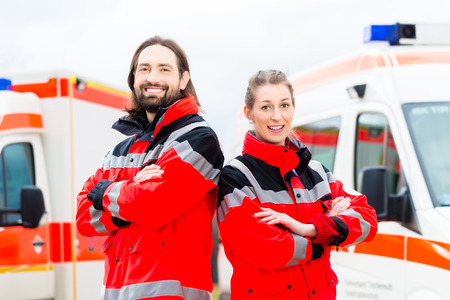 Emergency doctor and nurse standing in front of ambulance  photo