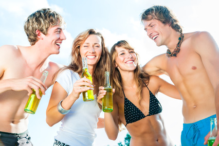Group of very beautiful people celebrating on the beach in the summer of their lives photo