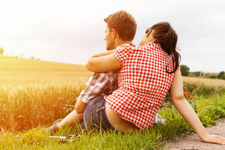 Young fitness couple doing sports outdoors, making a break from hiking in summer  photo