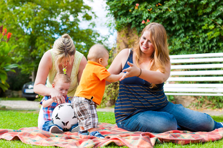 Happy young mother and grandmother sitting with their children and grandchildren in a park outdoors on bench photo