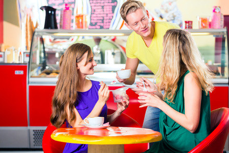 Friends meeting in ice cream parlor or cafe with cappuccino and ice-cream photo