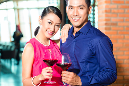 Portrait of Asian couple with a glass of red wine photo