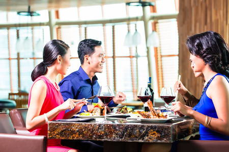Asian Friends eating and drinking wine in restaurant photo