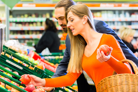 Couple selecting apples while grocery shopping in supermarket  photo