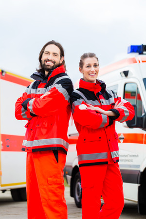 emergency call: Emergency doctor and nurse standing in front of ambulance