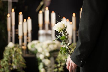 Religie, dood en dolor - man bij de begrafenis met witte roos rouwt om de dood