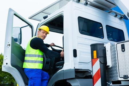 크레인 운전자 또는 운전사가 건물 또는 건설 현장에서 트럭으로 운전 스톡 콘텐츠