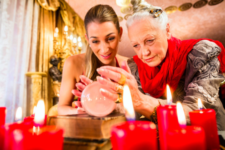 Female Fortuneteller or esoteric Oracle, sees in the future by looking into their crystal ball during a Seance to interpret them and to answer questions photo