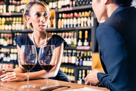 Asian Couple talking in a wine shop