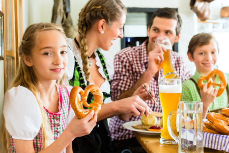 Bavarian girl wearing dirndl and eating with family in traditional restaurant  photo