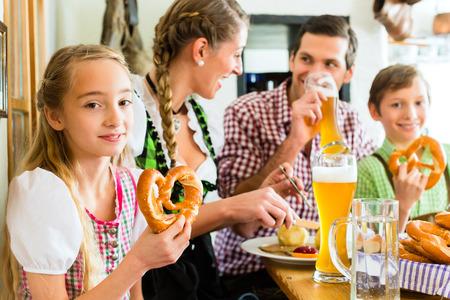 familia comiendo: Muchacha bávara lleva dirndl y comer con la familia en el restaurante tradicional