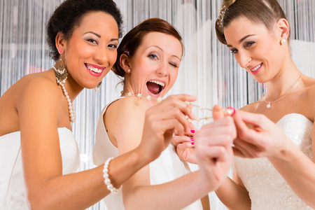 fitting in: Women having fun while bridal gown fitting in wedding fashion store Stock Photo
