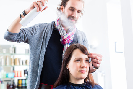 Male coiffeur giving women hairstyling with hairspray in shop photo