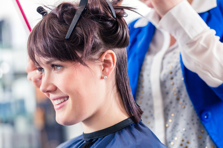 Female coiffeur divide women hair in sections with clips in shop photo