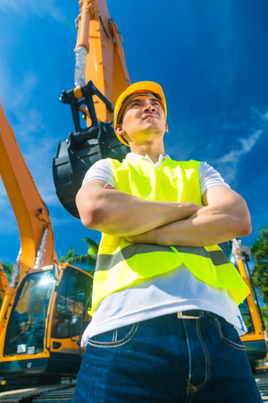 Asian worker standing in front of construction machinery of building site or rental company photo