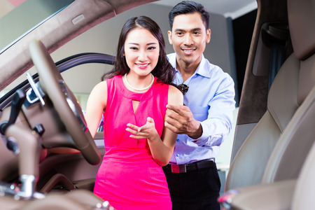 Asian couple choosing luxury car in auto dealership looking at the interior photo