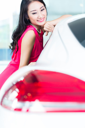 Asian Chinese woman buying SUV car marveling at the beauty of the auto  Stock Photo