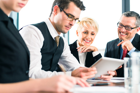 Business - meeting in office, the businesspeople with boss and team are discussing a document on tablet and Laptop computer Stock Photo