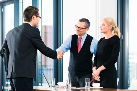 De negocios - hombre joven en la entrevista de trabajo para la contratación, da la bienvenida, jefe o mayor y su asistente femenina en su oficina