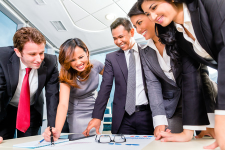 Asian Businesspeople standing around a table photo