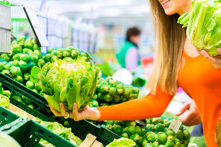 Woman buying cauliflower while shopping in supermarket  photo