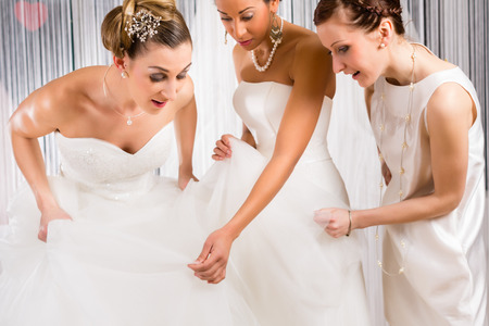 try: Women trying on together bridal gown in wedding fashion store