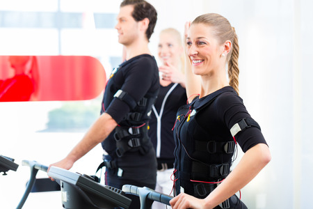Female coach giving man and woman ems electro muscular\ stimulation exercise