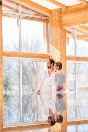 window treatments: Couple on pool looking relaxed throw window of wellness spa wearing bath robe Stock Photo