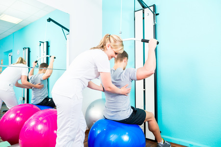 physical: Patient at the physiotherapy doing physical exercises with therapist in sport rehabilitation Stock Photo